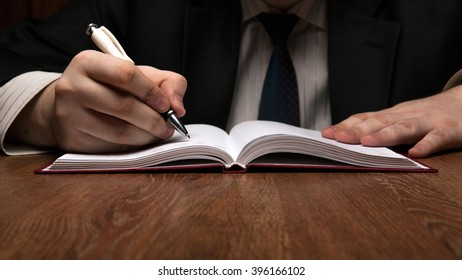 man running with diaries with pen close up