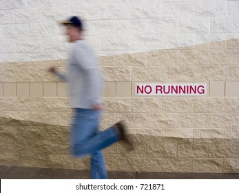 Man running in front of a No Running sign.