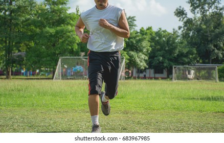 Man running in grass field for exercise. Healthy lifestyle. Handsome man running on grass field in morning