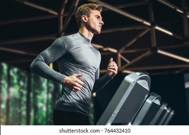 Man running in a gym on a treadmill concept for exercising, fitness and healthy lifestyle