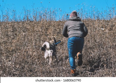 Man is running up the hill with Husky dog