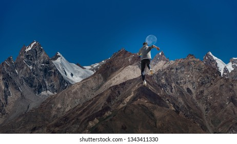 A Man running up hill to the peak of the mountain with blue sky and the moon in background, run to the future and hope concept.