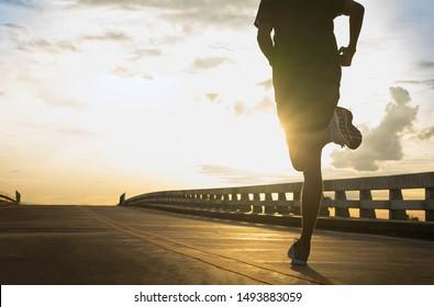 Man running jogging on bridge road. Health activities, Exercise by runner.