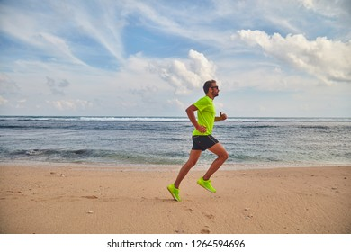 Man running / jogging on a tropical exotic beach.