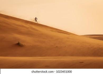 Man running joyfully on dunes of desert Sahara in Morocco in a storm day