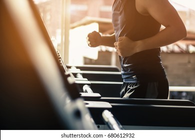 Man running in a modern gym on a treadmill concept for exercising, fitness and healthy lifestyl.lowkeylight.vintage tone.selective focus.