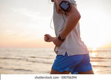 Man running with music player and smartwatch on his wrist