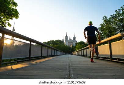 A man is running at Notre-Dame de Fourviere in Lyon on a beautiful spring morning. Lyon, France.
