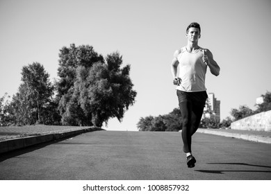 Man running on asphalt road on sunny summer day on blue sky. Success, goal and future concept