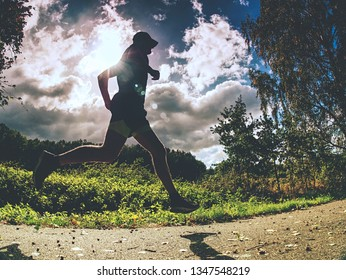 Man running on asphalt track. Athlete running fast in a park with dense trees in the background.