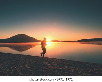 Man running on the beach against the backdrop of a beautiful sunset. Sand of mountain lake with deep foot trails.