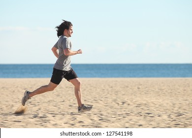 Man running on the beach with the sea in the background