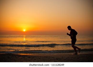 Man running on the beach at sunrise