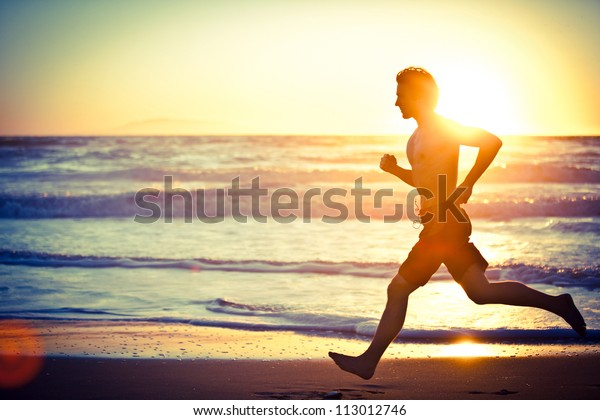 Man running on the beach at sunset - female version in portfolio