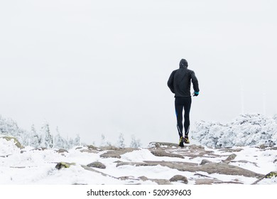 man running on the cold mountain trail in winter with snow