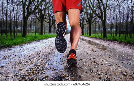 Man running on a dirty road in a rainy day
