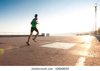 Man running on the promenade at the seaside. Motion blur on the runner, a lot of copy space (Nice, France, Europe).