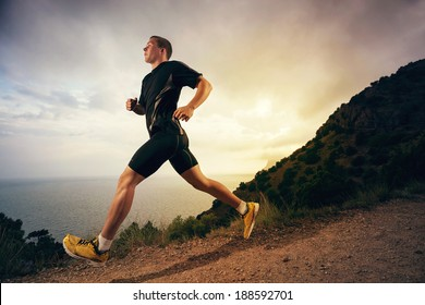 Man running on a rural road during sunset in the mountains