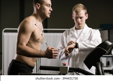 Man running on treadmill during medical test and medic in white uniform