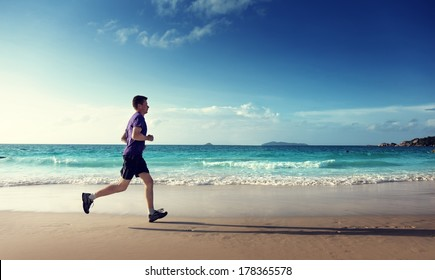 Man running on tropical beach at sunset