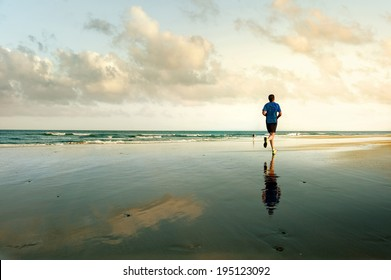 Man running on tropical beach at sunset. Maspalomas. Gran Canaria.