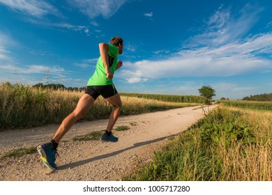 The man running on the unpaved country road among the fields in Slovenia