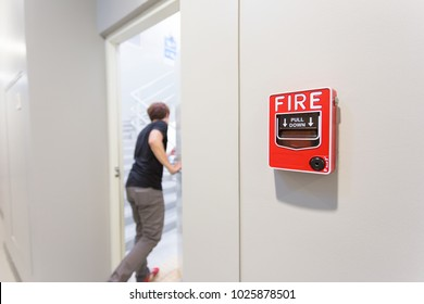 The man running open emergency exit door is and fire alarm on the wall next to the door.