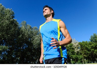 Man running outdoor. Handsome athlete exercising workout on park. Copyspace.