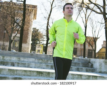 man running outside in the city park