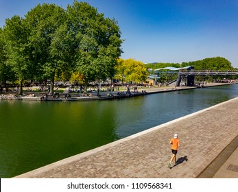 A man running in Paris at La Villette while people are having picnic