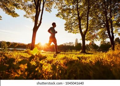 MAn running in park during sunny summer sunset