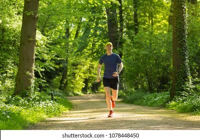 Man running in a park on a summer morning. Lyon, France.