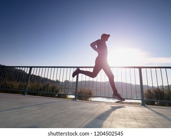 Man is running quickly on the shore bridge. Silhouette of active man exercising and stretching on the lake street. Healthy lifestyle. Alone young fitness man.