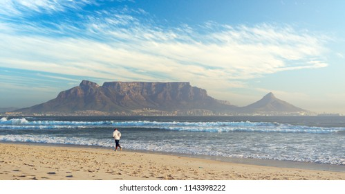 Man is running at sand beach on background of Table Mountain, Cape Town