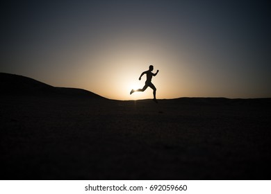 man running silhouette on sunset background, young caucasian run in mountain