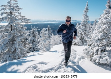 Man running in the snow on top of a mountain on a beautiful winter day