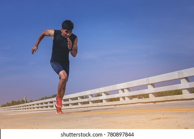 Man running sprinting on road. Fit male fitness runner during outdoor workout.