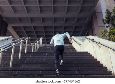 Man running up the stairs of a building. Athlete climbing stairs as part of his physical training.