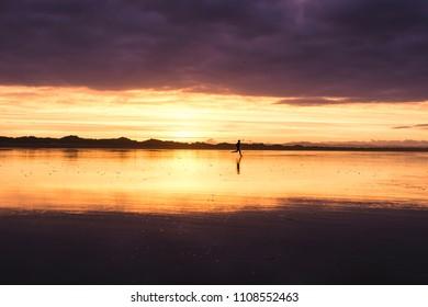Man running at sunset into the sea on an empty beach.