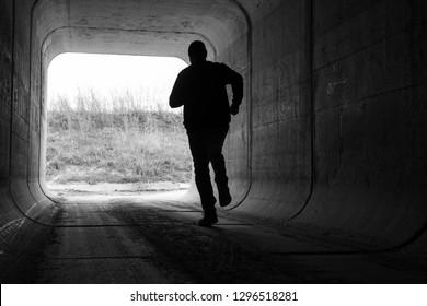man running through dark tunnel escaping