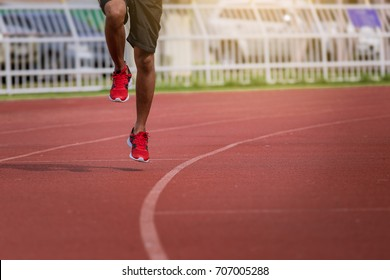 man running in the track. Fit male fitness runner jogging in stadium