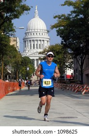 Man running in a triathlon in front of the Capitol building, Madison, Wisconsin