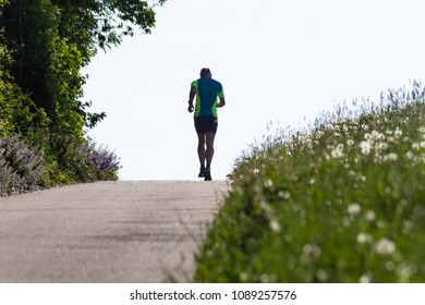 man running uphill springtime morning in south german rural countryside nature meadow