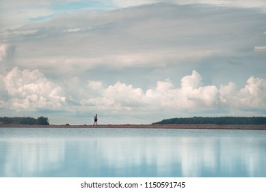 A man runs along the shore. A picturesque place. Dramatic clouds after a thunderstorm