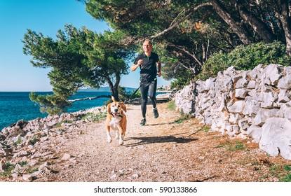 Man runs with dog near the sea