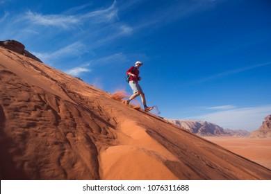 A man runs down the sand dune in the Wadi Rum desert, Jordan