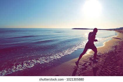 Man runs fast on the beach at dawn