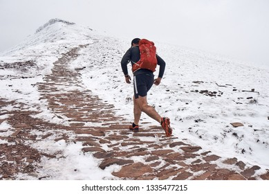 A man runs up a snow covered mountain in mid winter