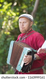 A man in a Russian national costume playing the accordion on a Slavic holiday
