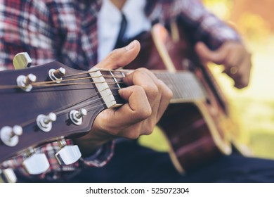 Man 's hand playing acoustic guitar, folk song. Nature background.